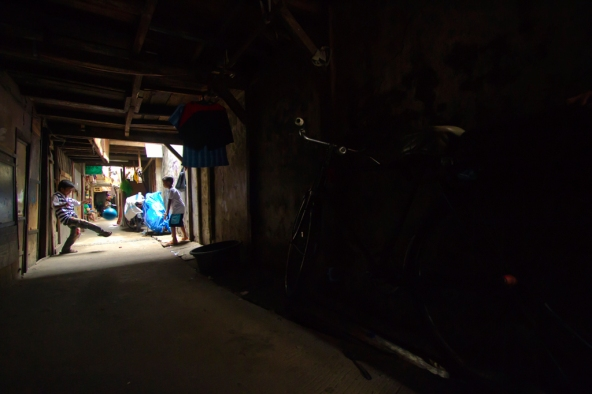 rumah-rumah kecil yang bertingkat itu, selain menutup sinar matahari, juga memberi batas pada ruang bermain anak-anak tambora